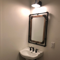 For lovers of the modern with a quirky twist, this custom-made bathroom mirror with black pipes represents the modern, industrial style perfectly!