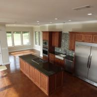 A beautiful kitchen with gorgeous colored cabinets, stainless steel double refrigerator and an open view.