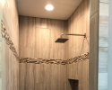 We tiled this shower with long subway tiles accompanied by an accent tilework display.